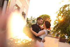 Bridal couple embracing in sunlight. Beautiful bridal couple embracing in sunlight Royalty Free Stock Photos