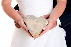 Bridal couple holding a stone- heart together Stock Photography