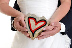 Bridal couple holding a stone- heart together Stock Photos