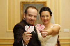 Bridal couple holding two paper hearts Stock Photo