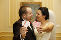 Bridal couple holding two paper hearts Royalty Free Stock Image
