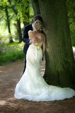 A Bridal Couple Kissing in Clandestine. A Bridal Couple Kissing in Clandestine and you only see the back of the bride and her beautiful mermaid wedding gown and Stock Photo