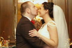 Bridal couple kissing. Reflection in mirror, selective focus royalty free stock photography