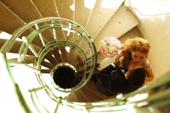 Bridal couple kissing on a spiral staircase. Groom and bride kissing on a spiral staircase Stock Photos