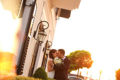 Bridal couple kissing in sunlight. Beautiful bridal couple kissing in sunlight Royalty Free Stock Image