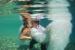 Bridal couple kissing underwater stock photo