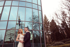 Bridal couple near building made of glass. Embracing Royalty Free Stock Images