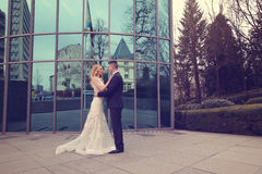 Bridal couple near building made of glass. Embracing Royalty Free Stock Photos