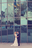 Bridal couple near building made of glass. Embracing Royalty Free Stock Photo