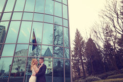 Bridal couple near building made of glass. Embracing Stock Photography