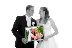 Bridal couple with photo of themselves Royalty Free Stock Photos