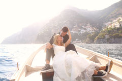 Bridal couple sitting in a wooden boat. On the sea Royalty Free Stock Photos