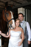 Bridal couple  in stable. Newlyweds with their horse in stable