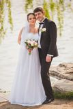 Bridal couple standing near lake Royalty Free Stock Images