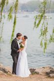 Bridal couple standing near lake Royalty Free Stock Image