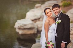 Bridal couple standing near lake Stock Images