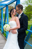 Bridal couple standing together on a blue bridge Stock Photos