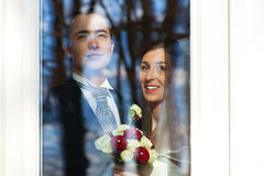 Bridal couple standing at the window at their wedd Stock Images