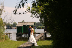 Bridal couple on a wooden bridge near the lake. Groom and bride on a bridge near the lake Royalty Free Stock Images
