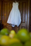 Bridal dress hanging from a door frame Royalty Free Stock Photos