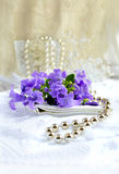 Bridal Dressing Table. Pearls and fresh flowers on a bridal dressing table against a vintage light background. Copy space Stock Photo