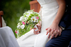 Bridal flowers. Beautiful bridal flowers in a womens hand holding the hand of her husband Stock Images