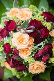 Bridal Flowers. Fresh red and yellow roses in bridal flowers with wedding rings on it Stock Photo