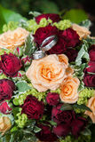 Bridal Flowers. Fresh red and yellow roses in bridal flowers with wedding rings on it Stock Images