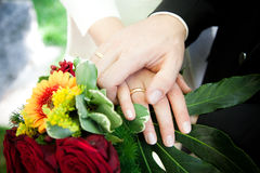 Bridal Flowers. Fresh red and yellow roses in bridal flowers with wedding rings on it Royalty Free Stock Photography