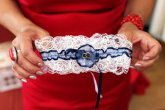 Bridal garter. White blue bridal garter for wedding in hands Royalty Free Stock Photo