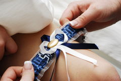 Bridal garter. A close up view of a bride's attendant putting a bridal garter on the leg of the bride before a wedding Stock Photo
