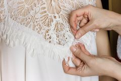 Bridal Gown Fitting. seamstress prepares dress to the fitting royalty free stock images
