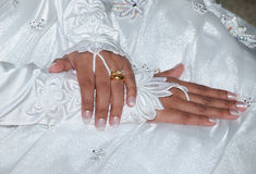 Bridal hand. Engagement and wedding band on the finger of a bride in her dress and veil, resting on her abdomen Royalty Free Stock Photos