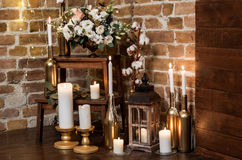 Bridal morning: burning candles on candlesticks and lantern. Many burning candles on candlesticks and lantern with fresh flower arrangement Royalty Free Stock Image