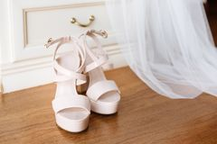 Bridal pink shoes standing in front of the nightstand. Bridal veil falling down from the nightstand. Bridal morning concept in pastel colors royalty free stock image