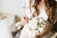 Bride in a white boudoir dress holding rustic bouquet. Bridal boudoir. Bridal morning concept in pastel colors stock photo