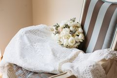 Wedding rustic bouquet and white dress on vintage striped chair. Bridal room interior. Bridal morning concept in pastel colors royalty free stock photography