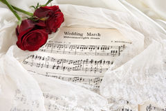 Bridal music. Sheet music of the Wedding March with roses and bridal veil stock photos