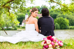 Bridal pair with bouquet on meadow at river Stock Photo