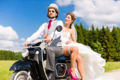 Bridal pair driving motor scooter wearing gown and suit. Wedding concept, bride and groom on motor scooter, she is showing her garter on leg royalty free stock photo