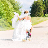 Bridal pair driving motor scooter wearing gown and suit Stock Images