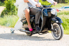 Bridal pair driving motor scooter wearing gown and suit Royalty Free Stock Photos