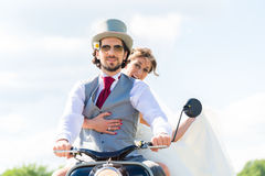 Bridal pair driving motor scooter wearing gown and suit Stock Image