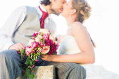 Bridal pair kissing on field Royalty Free Stock Photos