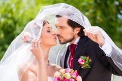 Bridal pair kissing under veil at wedding Stock Photography