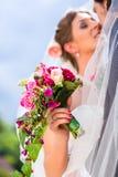 Bridal pair kissing under veil at wedding Stock Photo