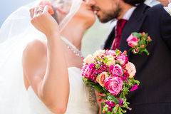 Bridal pair kissing under veil at wedding Royalty Free Stock Photos