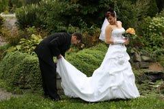 Bridal pair in park. Groom holding white bridal veil Stock Photo