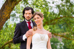 Bridal pair in park, groom holding bride Royalty Free Stock Photo