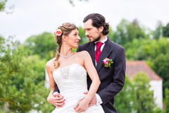 Bridal pair in park, groom holding bride Royalty Free Stock Photography